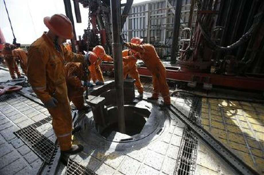 Oil workers lower the drill on the Centenario deep-water drilling platform off the coast of Veracruz, Mexico, in the Gulf of Mexico. The administration of Mexico's President Enrique Pena Nieto is pushing for an energy reform that will increase private investment in state-owned oil company Pemex and Mexico's oil. Photo: AP / AP