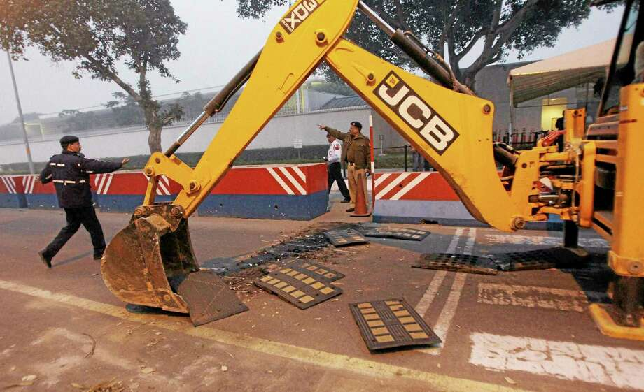 """Indian police remove barricades that had been erected as a safety measure outside the main entrance of U.S Embassy, reportedly in retaliation to the alleged mistreatment of New York based Indian diplomat Devyani Khobragade, in New Delhi, India, Tuesday, Dec. 17, 2013. The arrest and strip search of the Indian diplomat escalated into a major diplomatic furor Tuesday as India's national security adviser called the woman's treatment """"despicable and barbaric."""" (AP Photo) INDIA OUT Photo: AP / AP"""
