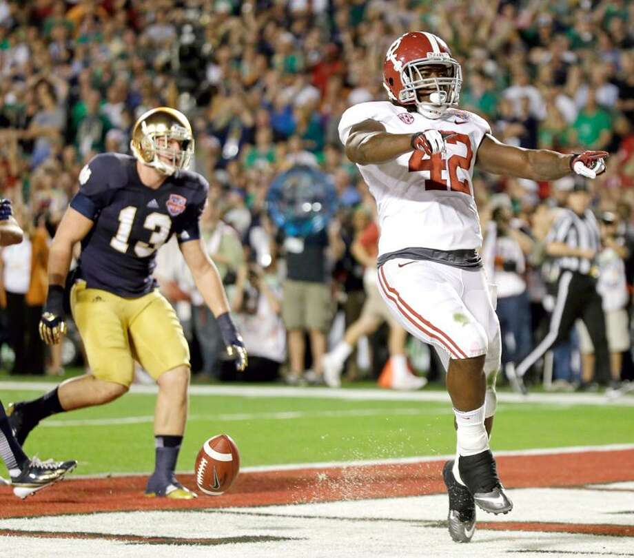 Alabama's Eddie Lacy (42) reacts after rushing for a touchdown during the first half of the BCS National Championship college football game against Notre Dame Monday, Jan. 7, 2013, in Miami. (AP Photo/David J. Phillip) Photo: AP / AP2013