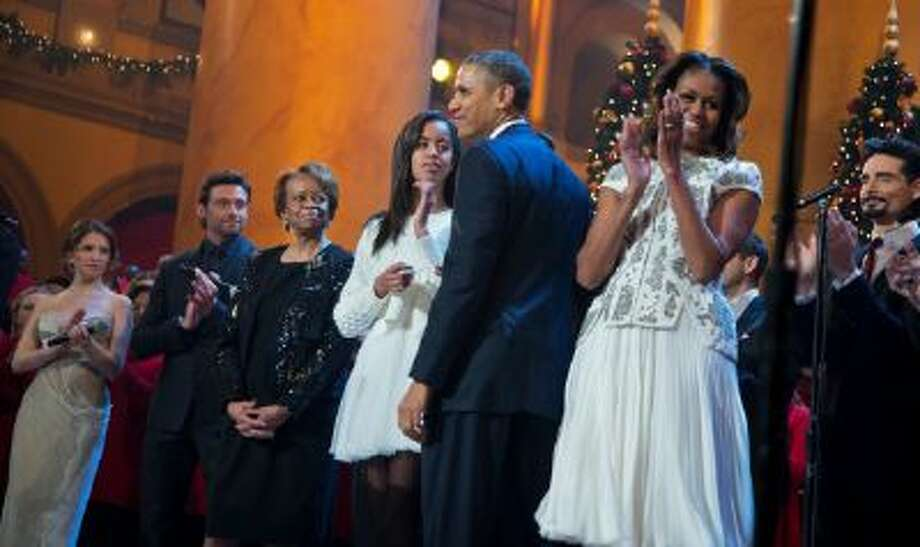 President Barack Obama, center, with first lady Michelle Obama, second from right, and their daughters Sasha and Malia, fourth from left, and mother-in-law Marian Robinson, third from left, join, from left; Anna Kendrick, host Hugh Jackman, and Kevin Richardson of the Backstreet Boys, right, during the annual 2013 Christmas in Washington presentation at the National Building Museum in Washington, Sunday, Dec. 15, 2013.