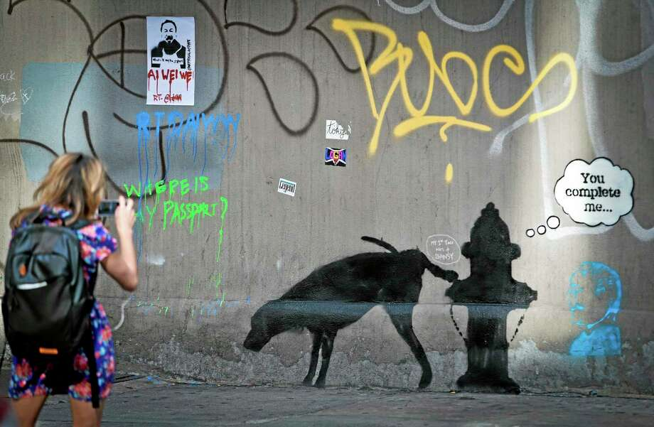 FILE - In this Friday, Oct. 4, 2013, file photo, graffiti by the secretive British artist Banksy, featuring a dog and a fire hydrant, draws attention on 24th Street, near Sixth Avenue in New York. Banksy wrote on his website that he had set up a stall in New York's Central Park on Saturday, Oct. 12, 2013, with original signed works, selling for only $60 apiece. His works typically sell for thousands of dollars. (AP Photo/Bebeto Matthews, File) Photo: AP / AP