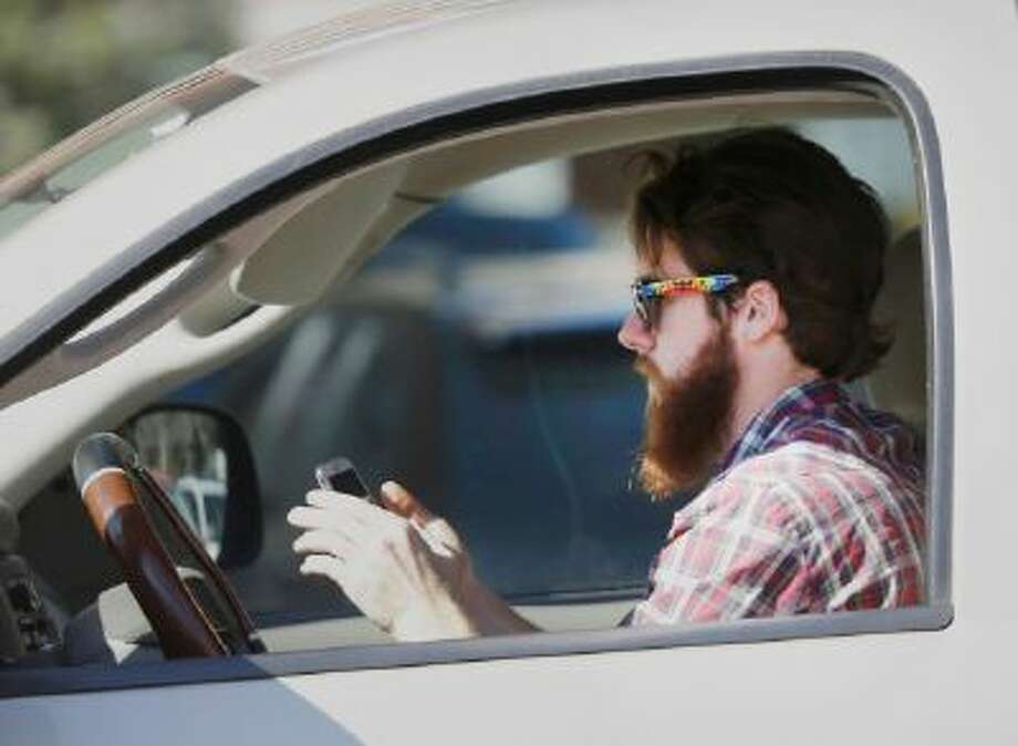 A man works his phone as he drives through traffic in Dallas.