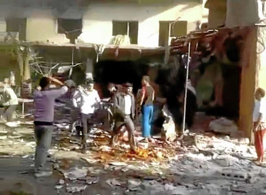 This image made from citizen journalist video posted by the Shaam News Network, which is consistent with other AP reporting, shows people evacuating a victim of a car bomb attack on a market in the town of Darkoush in Idlib province, Monday, Oct. 14, 2013. Syrian activist groups say the bombing in a rebel-held northwestern town has killed and wounded dozens of people. Car bombs are becoming more common in Syria's civil war, now in its third year. The conflict has killed more than 100,000 people.(AP Photo/Shaam News Network via AP video) Photo: AP / Shaam News Network