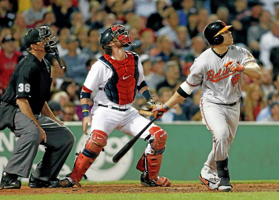 Baltimore Orioles' Chris Davis (19) watches his one-run double in front of Boston Red Sox's Jarrod Saltalamacchia, center, in the fifth inning of a baseball game in Boston, Thursday, Aug. 29, 2013. (AP Photo/Michael Dwyer) Photo: AP / AP