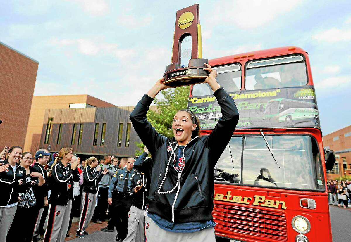 UConn's Stefanie Dolson carries the trophy during a parade through campus honoring the team's win in the women's NCAA Final Four college basketball championship.