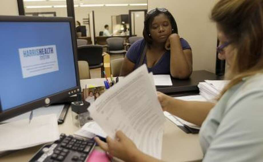In this Oct. 1, 2013 photo, Lillian Ardon, right, a certified application counselor with Harris Health System, helps Vanessa Danielle Cotton, left, with her paper Affordable Care Act marketplace application in Houston. Photo: AP / AP2013