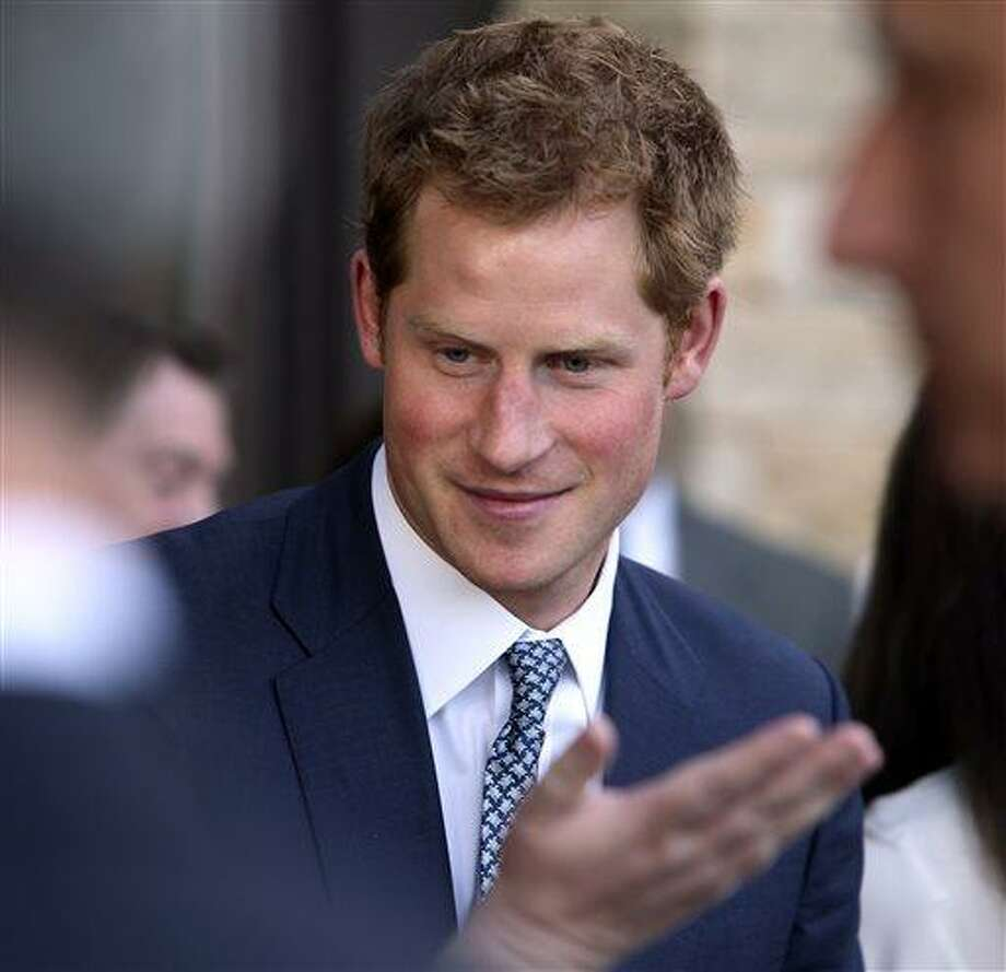 Britain's Prince Harry talks with a guest at a reception at the Sanctuary Golf Course in Sedalia, Colo., south of Denver on Friday, May 10, 2013. (AP Photo/Ed Andrieski, Pool) Photo: AP / AP Pool