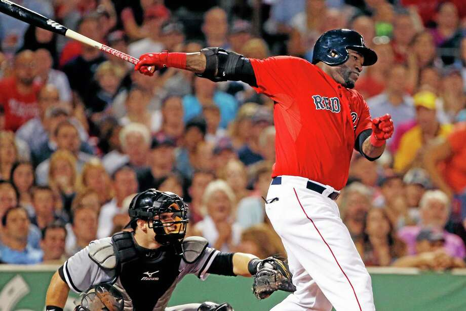 Red Sox designated hitter David Ortiz, right, hits a two-run single as Chicago White Sox catcher Josh Phegley watches in Friday's game. Photo: Elise Amendola — THE ASSOCIATED PRESS   / AP