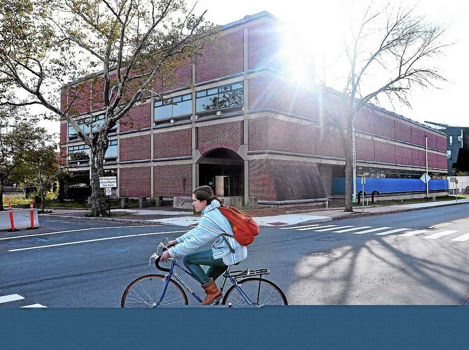 (Peter Casolino — New Haven Register)  A cyclist rides past Yale's Mudd library on Sachem Street in New Haven. pcasolino@NewHavenRegister Photo: Journal Register Co.