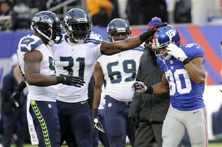 Seattle Seahawks' Kam Chacellor (31) pats New York Giants' Victor Cruz (80) as Cruz leaves the field with an injury during the second half of an NFL football game, Sunday, Dec. 15, 2013, in East Rutherford, N.J Photo: AP / FR51951 AP