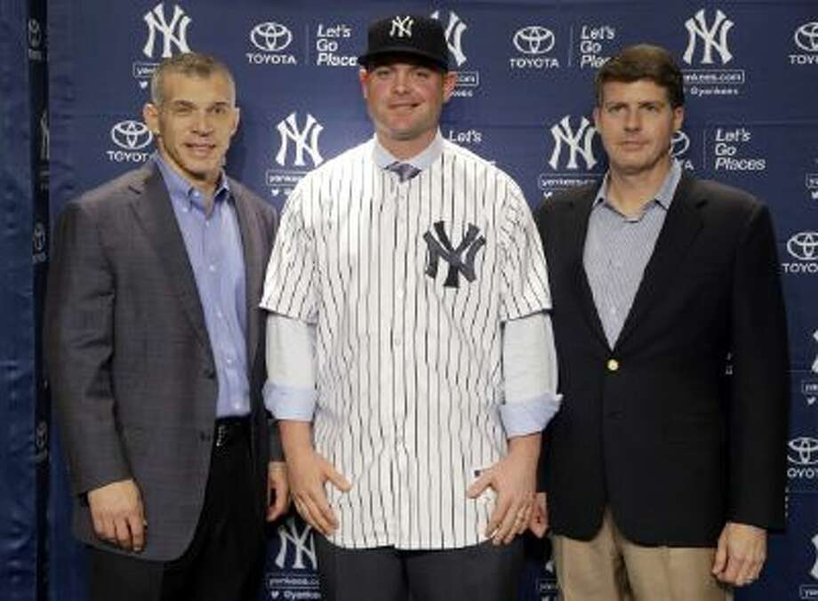 New York Yankees' Brian McCann, center, poses for a picture with manager Joe Girardi, left, and owner Hal Steinbrenner during a baseball news conference at Yankee Stadium in New York, Dec. 5.