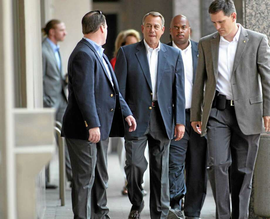 House Speaker John Boehner is escorted from the Grove Hotel to the Boise Centre to attend a fundraising lunch for Rep. Mike Simpson, Monday, Aug. 26, 2013 in Boise, Idaho. (AP Photo/Idaho Statesman, Darin Oswald) Photo: AP / Idaho Statesman