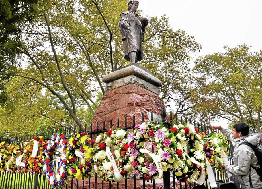 New Haven-- Naushad Ninzer helps to hang commemorative wreath by the statue of Christopher Columbus in Wooster Square.  Melanie Stengel/Register Photo: Journal Register Co.