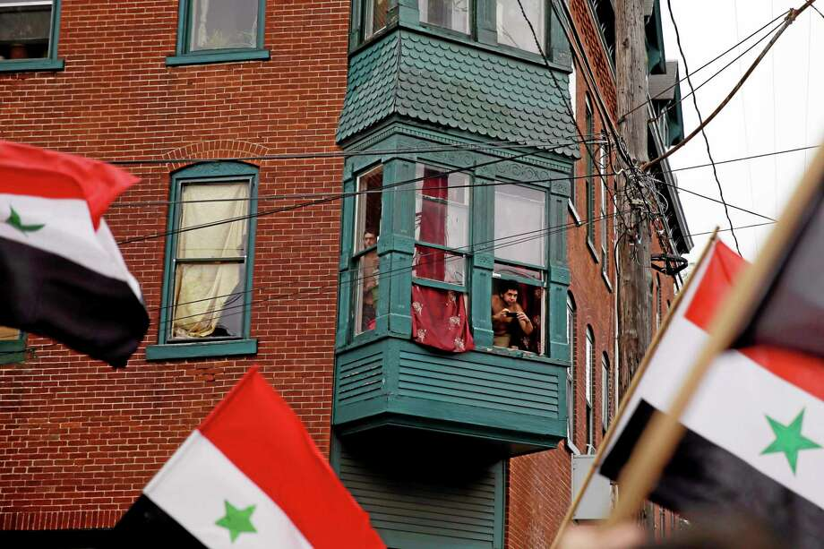 Residents watch from their windows as members of the local Syrian community rally against the United States' involvement in Syria, Friday, Aug. 30, 2013, in Allentown, Pa. President Barack Obama says he hasn't made a final decision about a military strike against Syria_but is considering a limited and narrow action in response to a chemical weapons attack that he says Syria's government carried out last week. (AP Photo/Matt Slocum) Photo: AP / AP