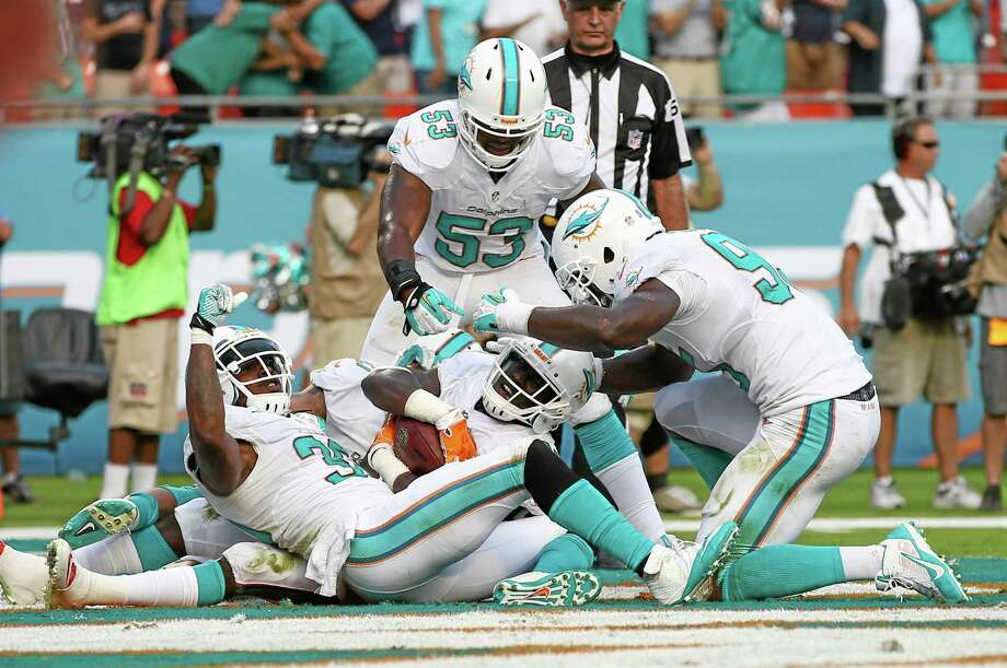 From left, Chris Clemons, Michael Thomas, Jelani Jenkins and the Dolphins defeated the Patriots 24-20 on Sunday in Miami. Photo: J Pat Carter — The Associated Press   / AP