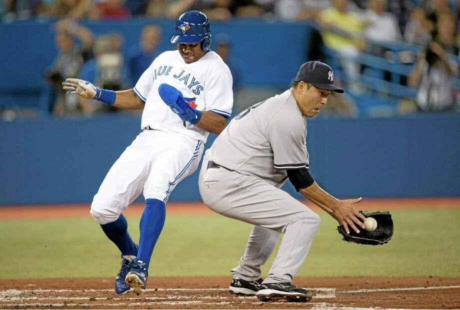Toronto Blue Jays' Rajai Davis, left, scores behind New York Yankees pitcher Hiroki Kuroda during first-inning action in Toronto. Photo: Frank Gunn — The Canadian Press/The Associated Press   / The Canadian Press