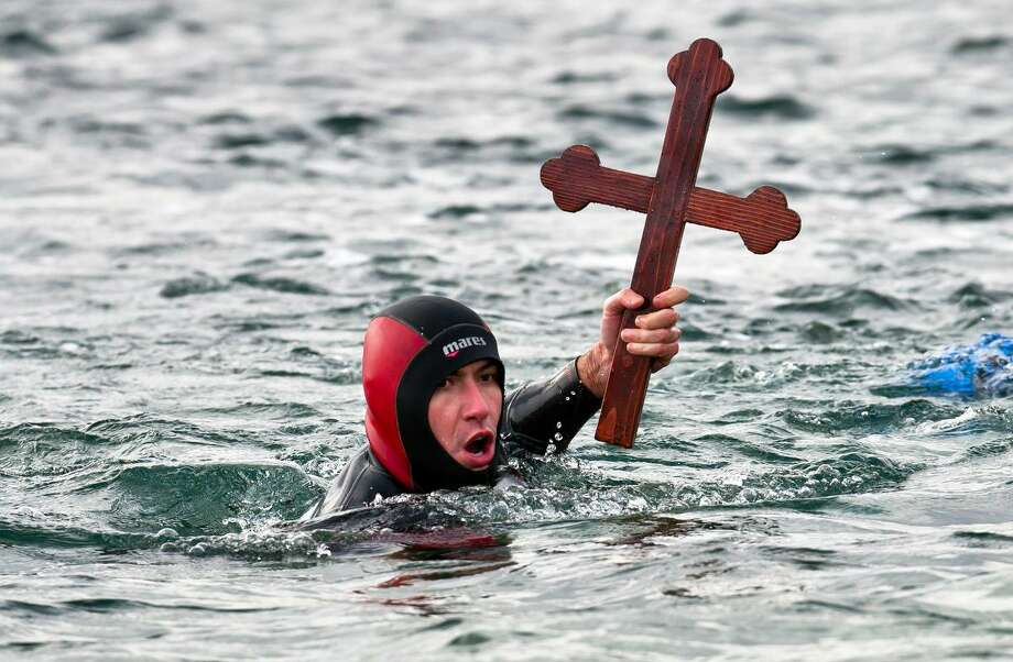 A swimmer lifts a wooden cross retrieved from the Black Sea after an Epiphany religious service in Constanta, Romania, Sunday, Jan. 6, 2013. Thousands attended the celebration in the Black Sea port town. (AP Photo/Vadim Ghirda) Photo: ASSOCIATED PRESS / AP2013