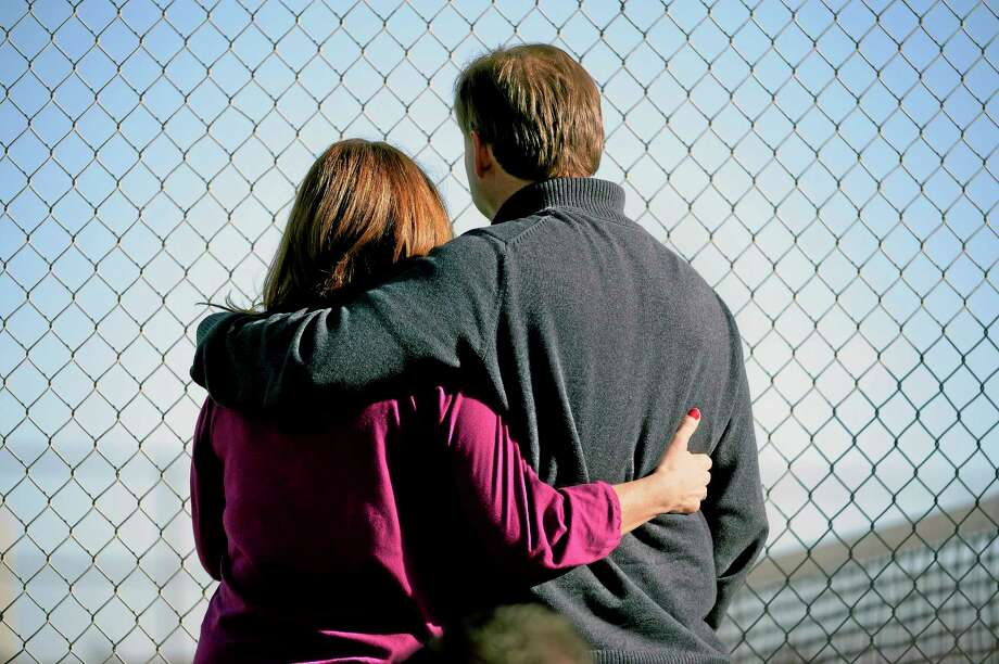 Parents stand along the tennis court fence hoping to see if their child is standing outside on the football field after a gunman was spotted inside Arapahoe High School Friday in Centennial, Colo. Authorities said the gunman shot two students and then turned the gun on himself. School.  AP Photo/The Denver Post, John Leyba Photo: AP / The Denver Post