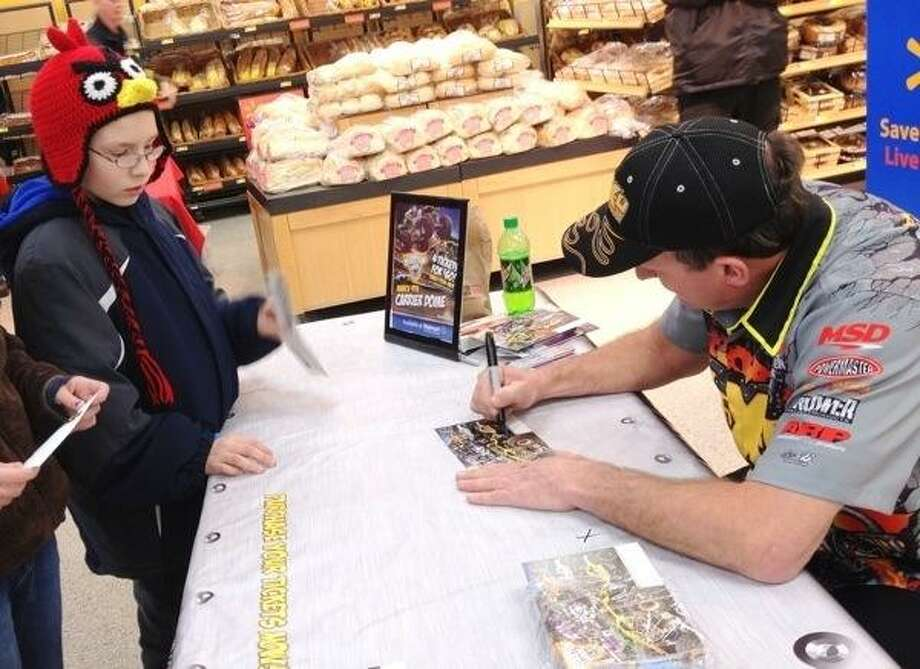 John Haeger @OneidaPhoto on Twitter/Oneida Daily Dispatch Nate  Hoose of Durhamville looks on as Max-O driver Tom Meents signs an autograph for him  Walmart on Thursday, March 7, 2013 in Oneida.