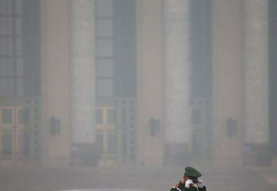 A Chinese paramilitary policeman adjusts his hat against the Great Hall of the People, on a polluted day in Beijing. Photo: AP / AP