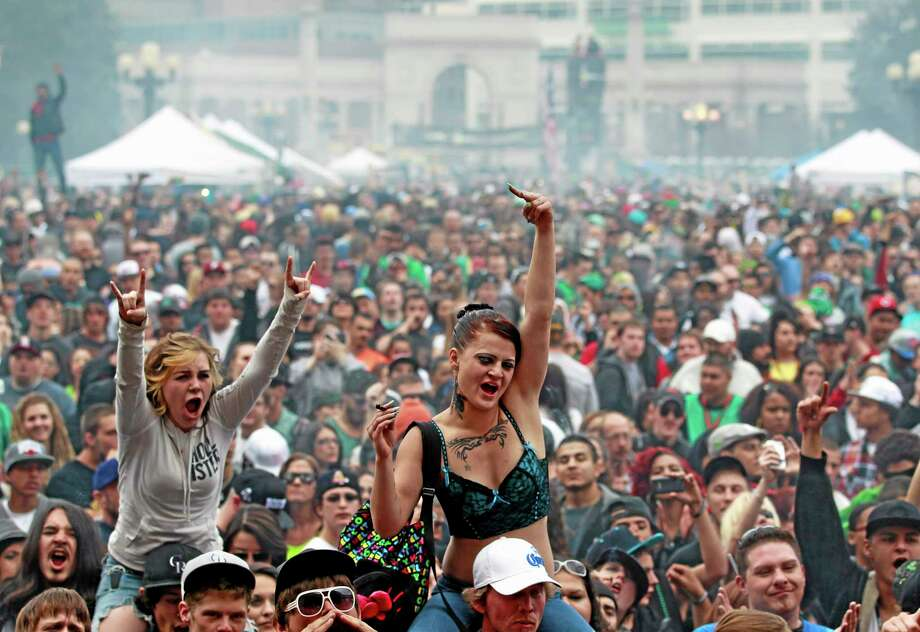 FILE - In this April 20, 2013 file photo, members of a crowd numbering tens of thousands smoke marijuana and listen to live music, at the Denver 420 pro-marijuana rally at Civic Center Park in Denver. The U.S. government said Thursday, Aug. 29, 2013 that the federal government will not make it a priority to block marijuana legalization in Colorado or Washington or close down recreational marijuana stores, so long as the stores abide by state regulations. (AP Photo/Brennan Linsley, File) Photo: AP / AP