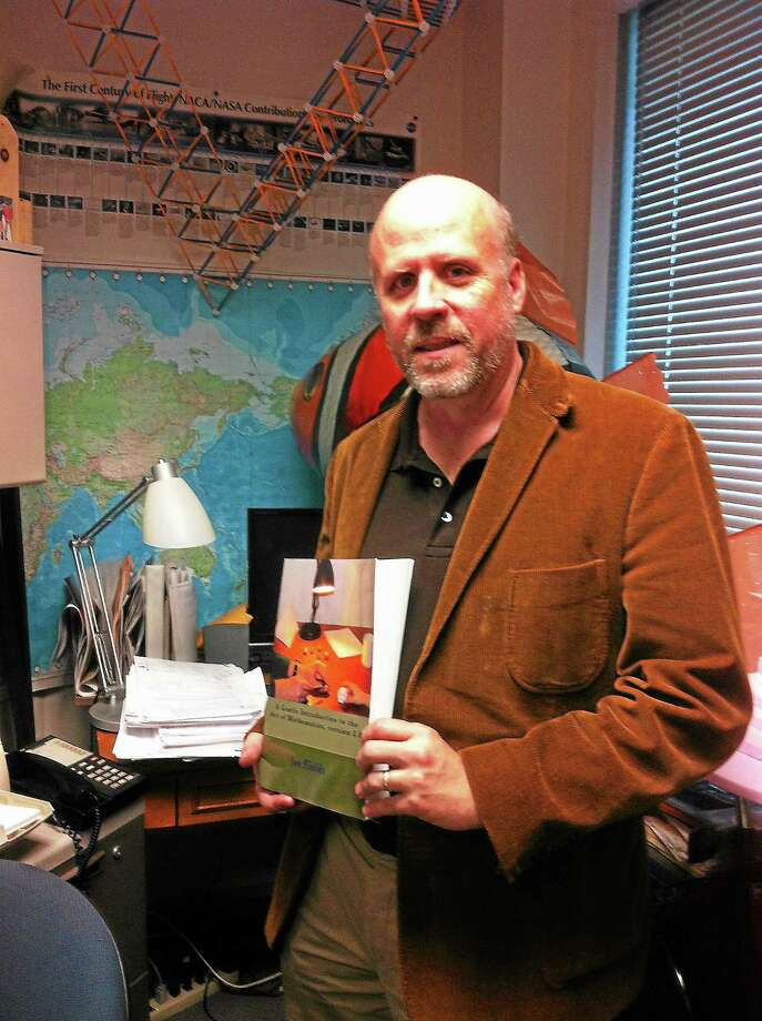 Professor Joseph Fields of Southern Connecticut State University holding a printed copy of his open-source math textbook. Photo: Journal Register Co.