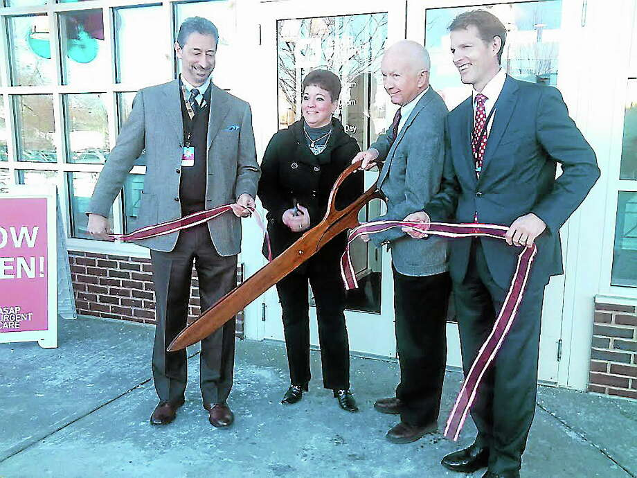 From left to right: Larry Earl, chief medical officer for ASAP Urgent Care, Tina LaRiviere, associate director of operations for ASAP, First Selectman Fillmore McPherson, and Traver Hutchins, chief executive officer for ASAP. Photo: Journal Register Co.