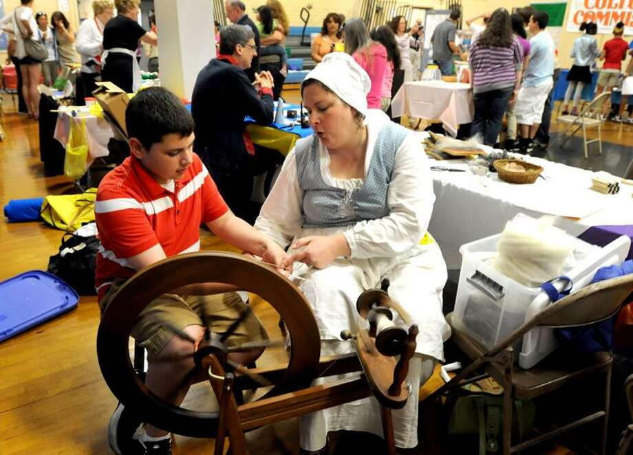 Michael LaRovera, 12, a Ansonia Middle School 7th-grader, left, learns how to spin wool into yarn using a spinning wheel as taught by Tina Carlson of the Derby Historical Society, right, during the Ansonia Middle School annual Culture Fair Friday May 10, 2013 featuring ethnic food, music, art and more sponsored by the school's Human Relation Club.   Photo by Peter Hvizdak / New Haven Register Photo: New Haven Register / ©Peter Hvizdak /  New Haven Register