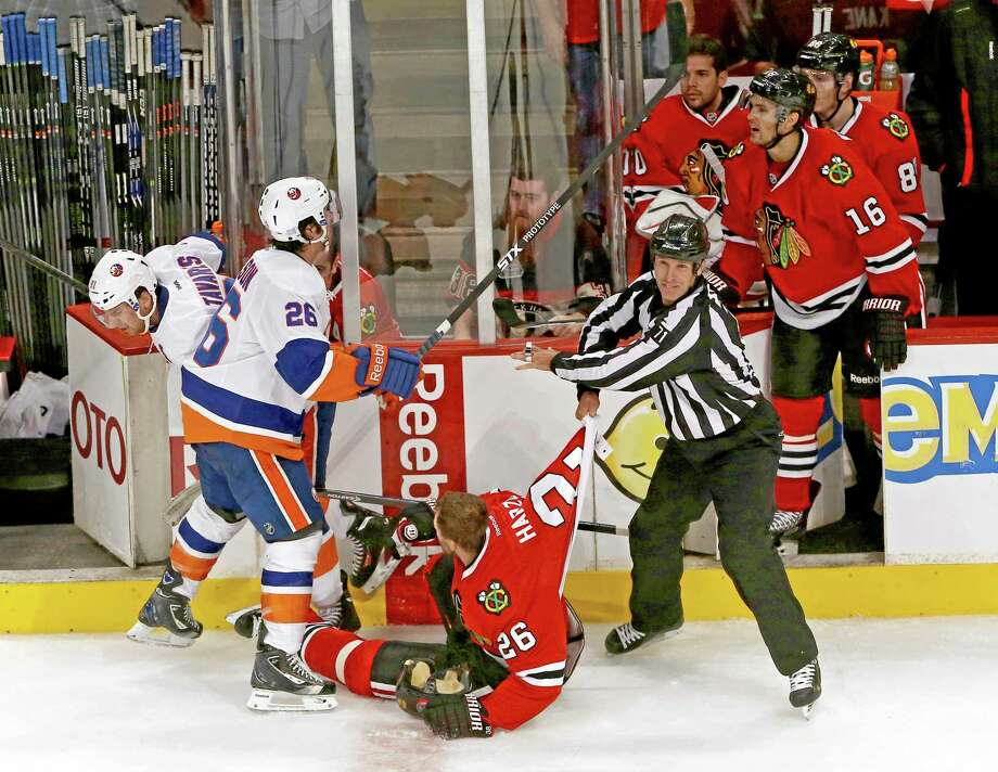 Linesman Brad Kovachik pulls the Chicago Blackhawks' Michal Handzus away from the New York Islanders' John Tavares as the Islanders' Matt Moulson gets into a shouting match with the Blackhawks' Marcus Kruger late in the third period. The Blackhawks defeated the Islanders 3-2 on Friday in Chicago. Photo: Charles Cherney — The Associated Press   / FR170067 AP