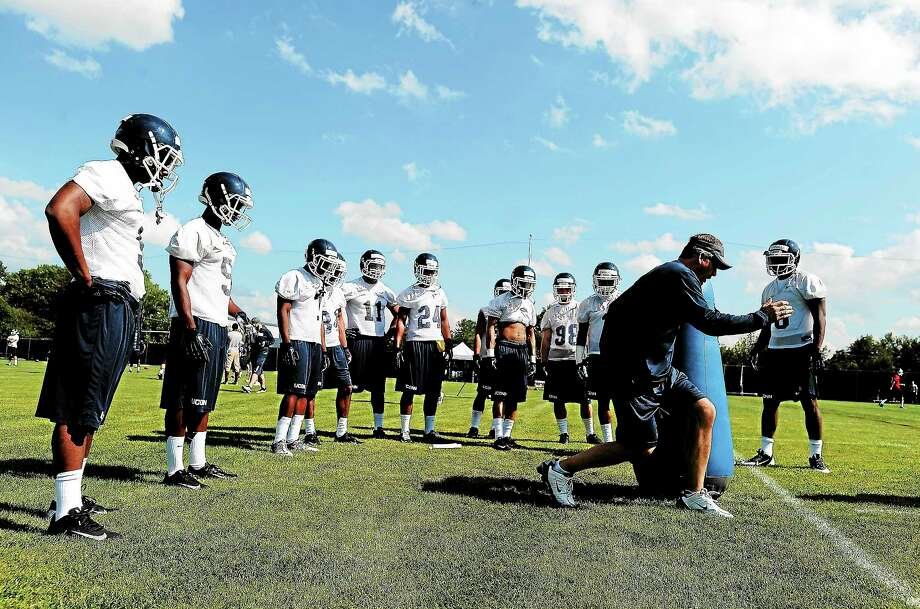 UConn offensive coordinator T.J. Weist demonstrates a drill during practice in Storrs on Aug. 2. Photo: Jessica Hill — The Associated Press   / FR125654 AP