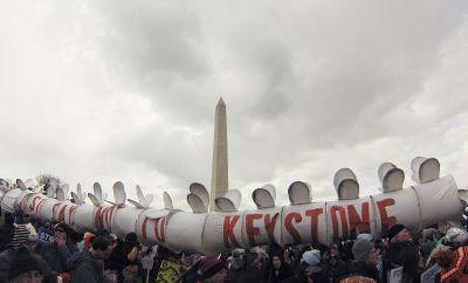 Demonstrators carry a replica of a pipeline during a march against the Keystone XL pipeline in Washington, February 17, 2013. Photo: REUTERS / X00058