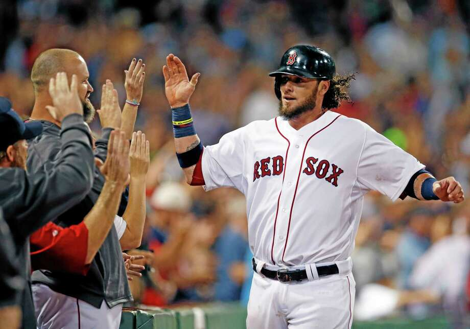 Boston Red Sox's Jarrod Saltalamacchia , right, receives high-fives after scoring on Mike Carp's pinch-hit single during the eighth inning of Wednesday's game against the Baltimore Orioles at Fenway Park in Boston. It proved to be the winning run as the Red Sox won 4-3. Photo: Elise Amendola — The Associated Press   / AP