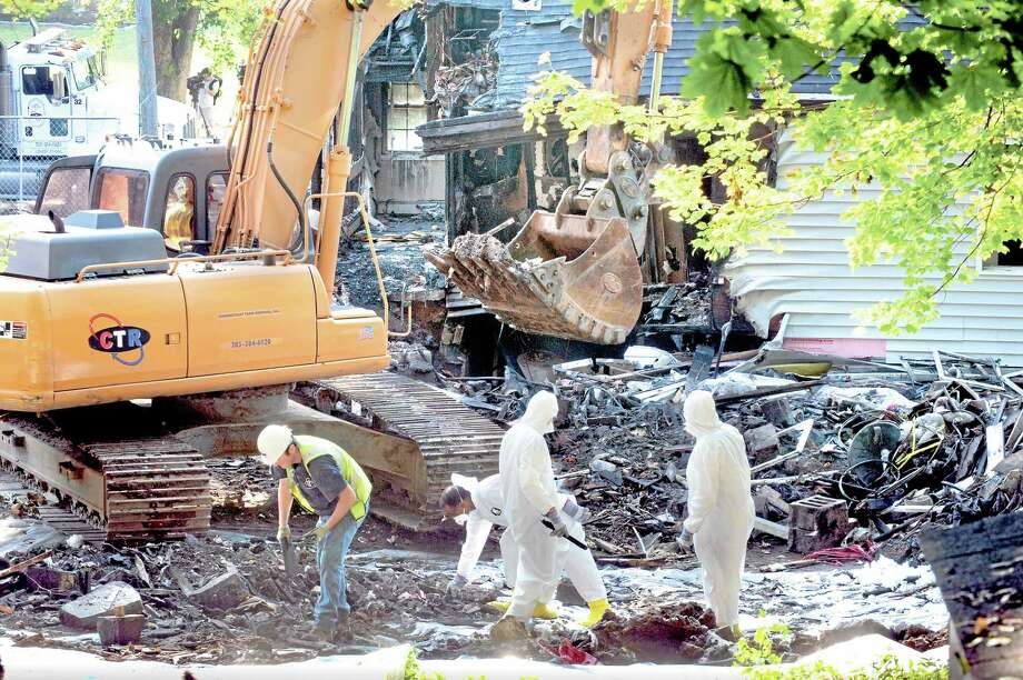 (vmWilliams — New Haven Register)DEEP personnel sift the debris field at the Charter Oaks Rd house in east Haven that was the site of a plane crash recently as the demollition of the house begins August 28, 2013. Photo: Journal Register Co.