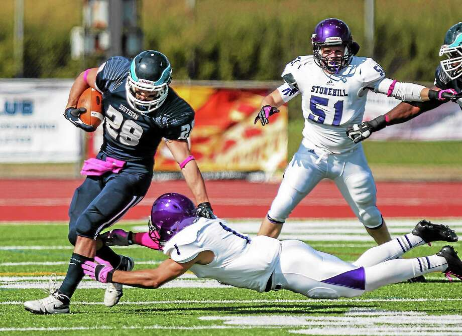 Southern Connecticut State running back John Moscatel escapes the tackle attempt from Stonehill cornerback Nate Morris during the Owls' 23-21 loss on Saturday in New Haven. Photo: John Vanacore — FOR THE REGISTER
