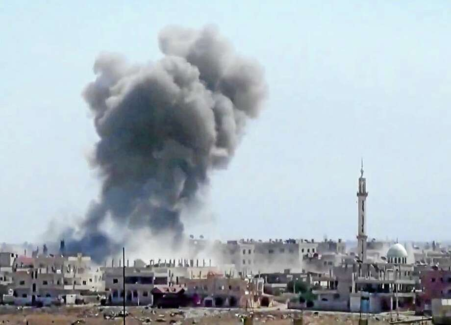 In this Tuesday, Aug. 27, 2013 image taken from video obtained from the Ugarit News, which has been authenticated based on its contents and other AP reporting, smoke rises from buildings due to heavy shelling in Daraa, Syria, Wednesday, Aug. 28, 2013. (AP Photo/Ugarit News via AP video) Photo: AP / Daraa City