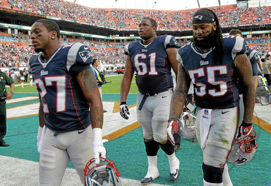 Patriots strong safety Tavon Wilson (27), tackle Marcus Cannon (61) and middle linebacker Brandon Spikes (55) walk off the field after they lost to the Dolphins 24-20 on Sunday. Photo: Lynne Sladky — The Associated Press   / AP