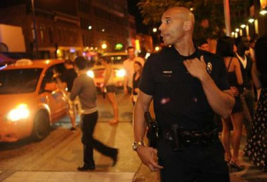 Denver police Officer Damon Bowser works off-duty at a club at 14th and Market streets last summer. (, The Denver Post)
