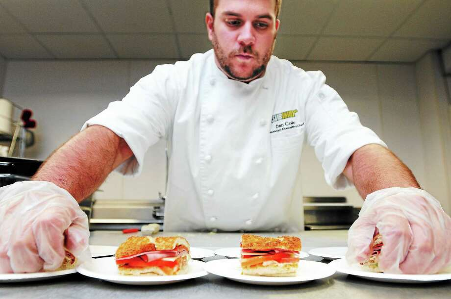 (Arnold Gold — New Haven Register)  Dan Cole, assistant executive chef,  prepares an Italian BMT on garlic bread in the test kitchen at Subway World Headquarters  in Milford Wednesday. Garlic bread is being introduced at Subway restaurants Sunday. Photo: Journal Register Co.