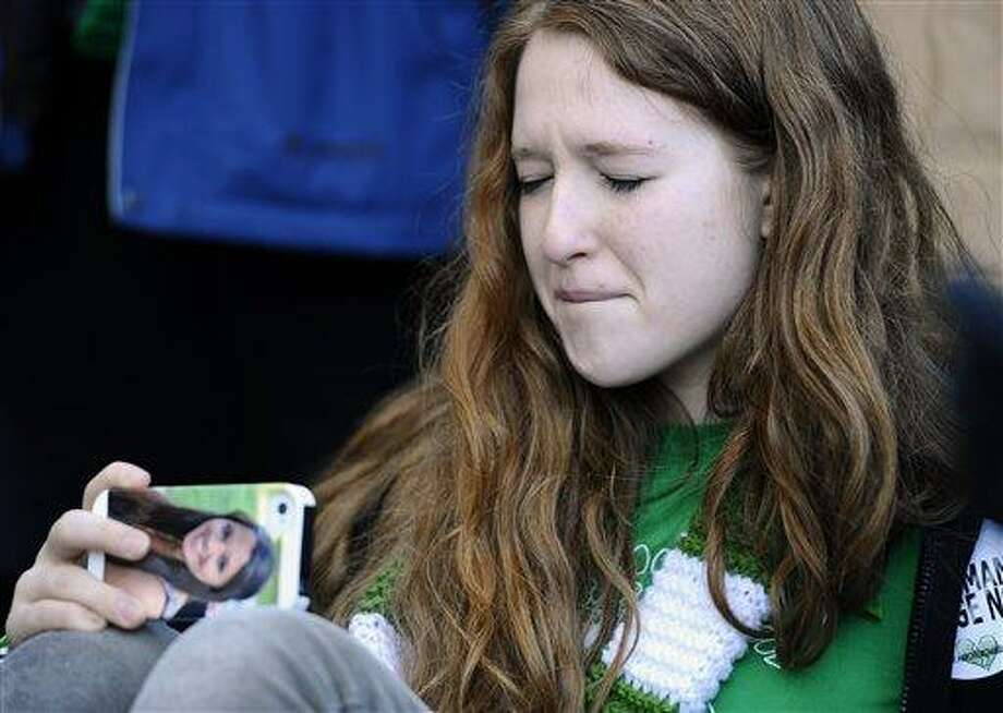 Sarah Clements of Newtown, Conn. uses a cell phone with a picture of Sandy Hook Elementary School shooting victim Victoria Soto on it,  to record the family speaking during a rally at the Capitol in Hartford, Conn., Thursday, Feb. 14, 2013. Thousands of people turned out to call on lawmakers to toughen gun laws in light of the December elementary school shooting in Newtown that left 26 students and educators dead. Clements' mother is a second grade teacher at Sandy Hook Elementary School and she knew Victoria Soto. (AP Photo/Jessica Hill) Photo: AP / FR125654 AP