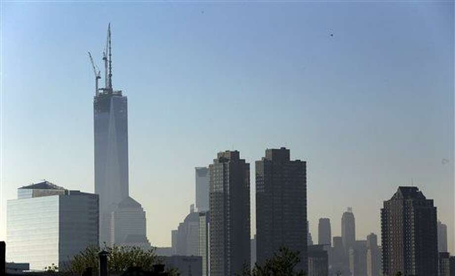 One World Trade Center stands at its full height above the New York City skyline in this view from the Heights neighborhood of Jersey City, N.J., Friday, May 10, 2013. A 408-foot spire was set into place at the top of the structure Friday, making the building a symbolic 1,776 feet tall. (AP Photo/Julio Cortez) Photo: AP / AP