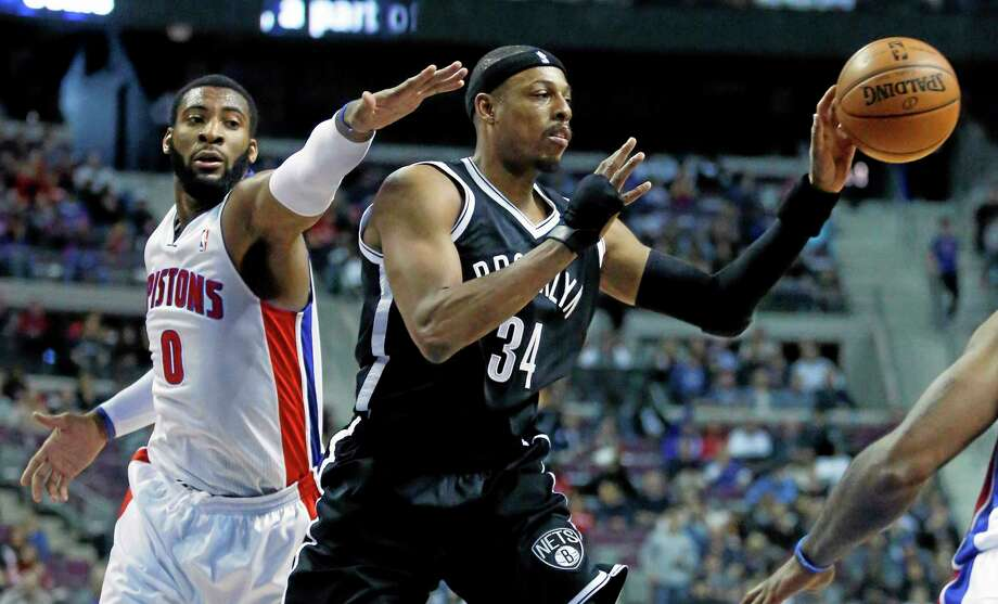 Brooklyn Nets forward Paul Pierce (34) passes the ball while being pressured by Detroit Pistons center and former UConn star Andre Drummond (0) during the first half Friday. Photo: Duane Burleson — The Associated Press   / FR38952 AP