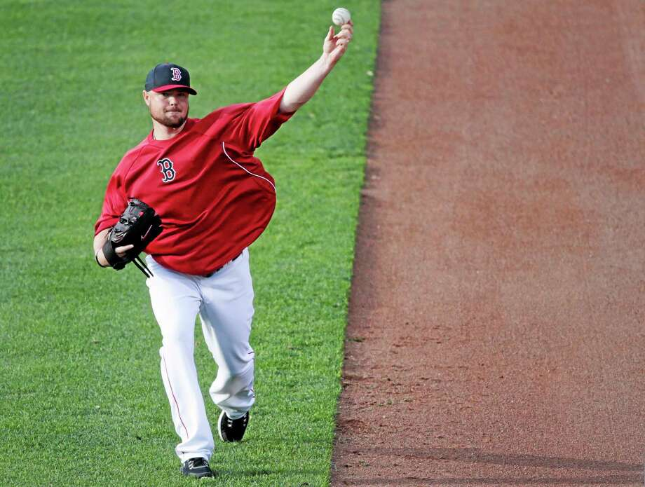 Red Sox starting pitcher Jon Lester warms up during a workout at Fenway Park in Boston on Friday. Lester is scheduled to start Game 1 of the AL championship series against the Detroit Tigers on Saturday. Photo: Charles Krupa — The Associated Press   / AP