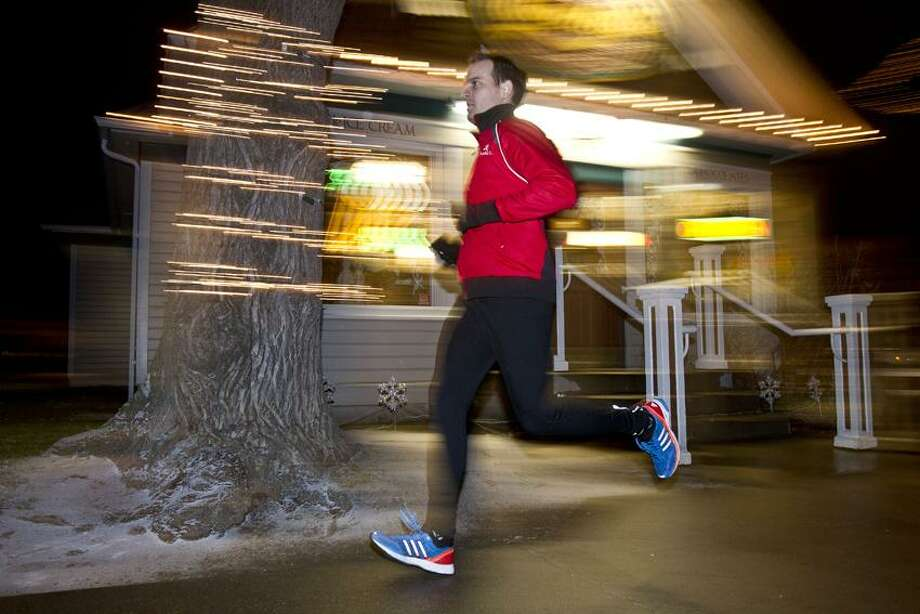 In this Dec. 26, 2012 photo, Boise attorney Tom Lloyd's runs along 13th street in Boise, Idaho. A busy young attorney with a new baby, Tom Lloyd realized in the summer of 2011 that he'd have a legitimate excuse nearly every day for not exercising. So he set a simple goal: Run at least a mile a day. (AP Photo/The Idaho Statesman, Chris Butler)  LOCAL TV OUT (KTVB 7) Photo: AP / Idaho Statesman
