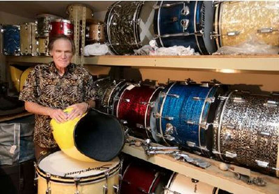 This photo taken Oct. 3, 2013 shows James Glay poses with his collection of vintage drums in Arlington Heights, Ill. Every passing month and unanswered resume dimmed Glay's optimism more. His career in sales was ended by a layoff. (M. Spencer Green/AP)
