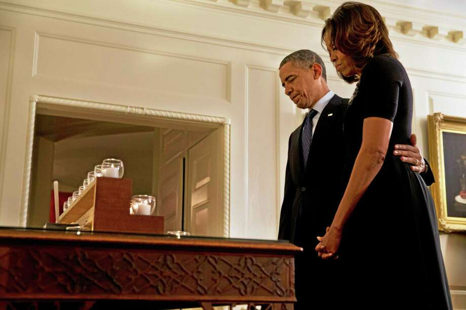 President Barack Obama and first lady Michelle Obama take a moment of silence in honor of the Newtown shooting victims on the one year anniversary of the tragedy, in the Map Room of the White House in Washington, Saturday, Dec. 14, 2013. (AP Photo/Jacquelyn Martin) Photo: AP / AP