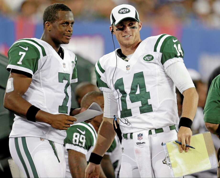 New York Jets quarterbacks Geno Smith (7) and Greg McElroy (14) talk during the first half of a preseason game against the New York Giants on Saturday in East Rutherford, N.J. Photo: Julio Cortez — The Associated Press   / AP