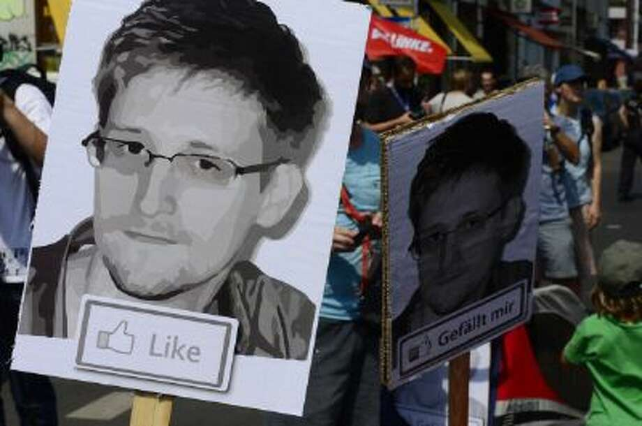 Demonstrators hold placards featuring an image of former US intelligence contractor Edward Snowden as they take part in a protest against the US National Security Agency (NSA) collecting German emails, online chats and phone calls and sharing some of it with the country's intelligence services in Berlin on July 27, 2013. (John MacDougall//AFP/Getty Images) Photo: AFP/Getty Images / 2013 AFP