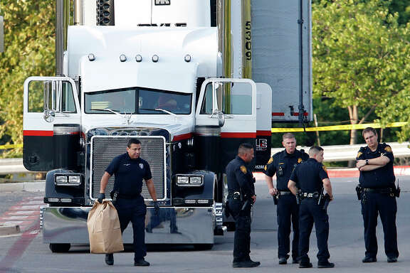 Law enforcement officers Sunday investigate the scene where eight  immigrants died in a tractor-trailer in San Antonio. Two more later died. (Edward A. Ornelas / San Antonio Express-News)