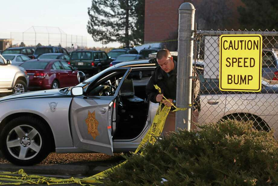 A trooper from the Colorado State Patrol pulls down the safety tape at an entrance to the student parking lot at Arapahoe High School in Centennial, Colo., on Saturday, Dec. 14, 2013. Investigators were working to find out what motivated a teenage gunman to enter his suburban Denver high school armed with a shotgun looking for a specific teacher a day earlier.  The 18-year-old shooter critically wounded a 15-year-old student and was later found dead in the school, apparently of a self-inflicted gunshot wound. (AP Photo/David Zalubowski)  (AP Photo/David Zalubowski) Photo: AP / AP