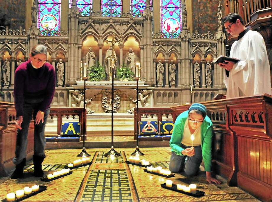 Trinity Episcopal Church on the Green Associate Rector Vicki M. Davis, left, and church member Kim Morris of Meriden, center, light 28 candles for those killed in the Dec. 14, 2012, Newtown shootings as Rector Luk De Volder, right, conducts a short service while the bells toll at 9:30 Saturday morning in New Haven. Photo: Peter Hvizdak — New Haven Register        / ©Peter Hvizdak /  New Haven Register